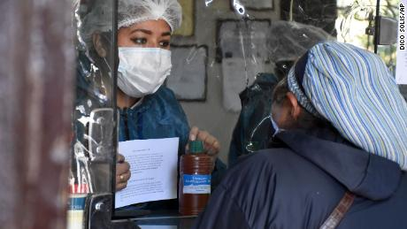 A woman buys chlorine dioxide at a pharmacy in Cochabamba on July 17, 2020.