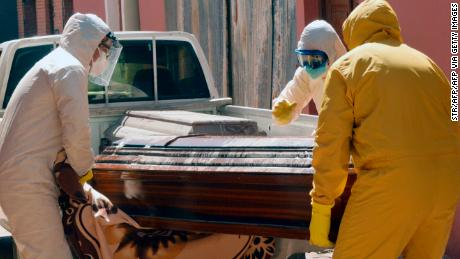 Medical workers carry a coffin containing a coronavirus victim in Cochabamba, Bolivia, on July 20.