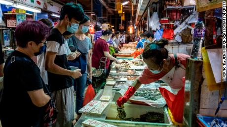 People wearing face masks are seen shopping at a fish stall inside a wet market on July 25, 2020 in Hong Kong.  (Photo by Vernon Yuen/NurPhoto via AP)