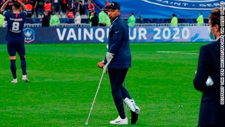 Paris Saint-Germain forward Kylian Mbappe walks with crutches after winning the French Cup final.