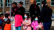 Children, some wearing face masks as a preventive measure, pick up free lunch at Kenmore Middle School in Arlington, Virginia on March 16, 2020, after schools in the area closed due to the coronavirus outbreak. - Stocks tumbled on March 16, 2020 despite emergency central bank measures to prop up the virus-battered global economy, as countries across Europe started the week in lockdown and major US cities shut bars and restaurants. The virus has upended society around the planet, with governments imposing restrictions rarely seen outside wartime, including the closing of borders, home quarantine orders and the scrapping of public events including major sporting fixtures. (Photo by ANDREW CABALLERO-REYNOLDS / AFP) (Photo by ANDREW CABALLERO-REYNOLDS/AFP via Getty Images)