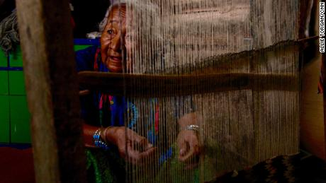 Marie Nez weaves a rug in her home on Navajo Nation.