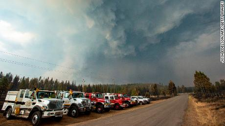 Firefighters look on as a smoke column collides with a thunderstorm cell near Susanville, California, July 21, 2020.