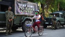 A resident rides her bicycle past armed soldiers along a street in Navotas in suburban Manila on July 16 after the local government reimposed a lockdown in the city due to increased COVID-19 infections.