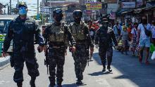 Elite policemen patrol a market while people shop during a government imposed enhanced quarantine as a preventive measure against the COVID-19 novel coronavirus in Manila on April 21.