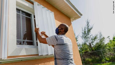Wendell Smith unfolds storm shutters at his home in Freeport in the Bahamas on Friday, July 31, 2020.