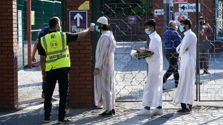 People wearing face masks have their temperatures checked before being allowed to go into Manchester Central Mosque on July 31.