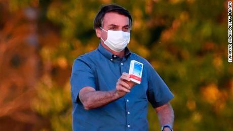 Brazilian President Jair Bolsonaro shows a box of hydroxychloroquine to supporters outside the Alvorada Palace in Brasilia, on July 23, 2020.