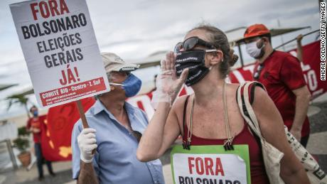"A demonstrator holds a sign that reads ""Go Away Bolsonaro, General elections now!"" during a rally against President Jair Bolsonaro and Governor of Rio de Janeiro Wilson Witzel amidst the coronavirus (COVID-19) pandemic at Copacabana beach on June 28, 2020 in Rio de Janeiro, Brazil."