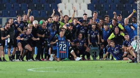 Atalanta players and staff celebrate with a Josep Ilicic shirt after the team's last game of the season.