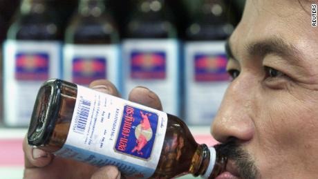 A Thai man drinks a bottle of Krating Daeng, an original Thai version of popular drink Red Bull, in a store in Bangkok in July 2001.