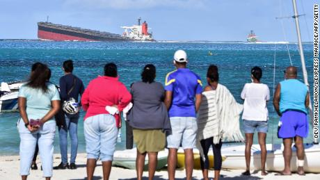 Bystanders look at MV Wakashio bulk carrier that had run aground and from which oil is leaking near Blue Bay Marine Park in south-east Mauritius on August 6, 2020. - The carrier, belonging to a Japanese company but Panamanian-flagged, ran aground on July 25 and its crew was evacuated safely. The ship was empty at the time but was carrying 200 tonnes of diesel and 3,800 tonnes of bunker fuel, according to the local press. (Photo by Dev Ramkhelawon / L'Express Maurice / AFP) / The erroneous mention[s] appearing in the metadata of this photo by Dev Ramkhelawon has been modified in AFP systems in the following manner: [Blue Bay Marine Park] instead of [Kigali, Rwanda]. Please immediately remove the erroneous mention[s] from all your online services and delete it (them) from your servers. If you have been authorized by AFP to distribute it (them) to third parties, please ensure that the same actions are carried out by them. Failure to promptly comply with these instructions will entail liability on your part for any continued or post notification usage. Therefore we thank you very much for all your attention and prompt action. We are sorry for the inconvenience this notification may cause and remain at your disposal for any further information you may require. (Photo by DEV RAMKHELAWON/L'Express Maurice/AFP via Getty Images)