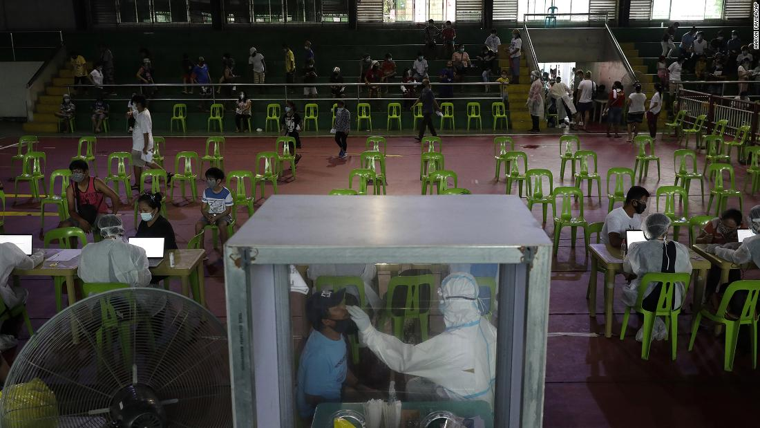 A health worker performs a Covid-19 test at a gymnasium in Navotas, Filippine, in agosto 6.