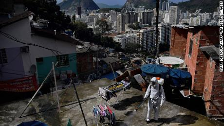 A volunteer disinfects a rooftop inside Santa Marta favela, in Rio de Janeiro on August 1.