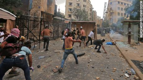 Lebanese protesters hurl rocks towards security forces.