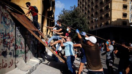 Protesters scale the walls sealing off parliament square in Beirut.