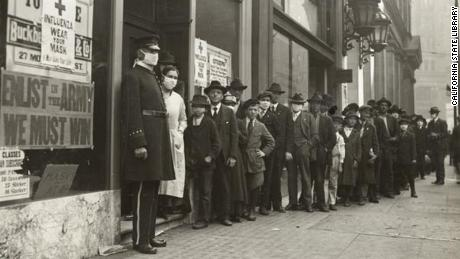 "A line of people waiting for flu masksin 1918 in San Francisco. A sign on the window bearing the Red Cross logo reads: ""Influenza. Wear Your Mask."""