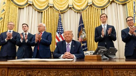 President Donald Trump, accompanied by from left, U.S. special envoy for Iran Brian Hook, Avraham Berkowitz, Assistant to the President and Special Representative for International Negotiations, U.S. Ambassador to Israel David Friedman, Trump's White House senior adviser Jared Kushner, and Treasury Secretary Steven Mnuchin, applaud in the Oval Office at the White House, Wednesday, Aug. 12, 2020, in Washington. Trump said on Thursday that the United Arab Emirates and Israel have agreed to establish full diplomatic ties as part of a deal to halt the annexation of occupied land sought by the Palestinians for their future state.
