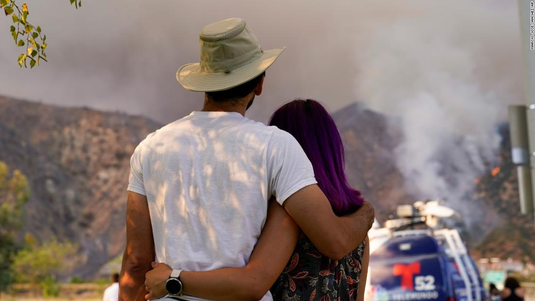 A couple watches the Ranch2 Fire from a distance on August 13.
