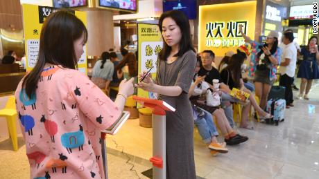 "Customers weigh themselves in the popular Hunan restaurant chain Chuiyan Fried Beef, in the city of Changsha. Signs around the restaurant say ""clean your plate"" and ""be thrifty and diligent."""