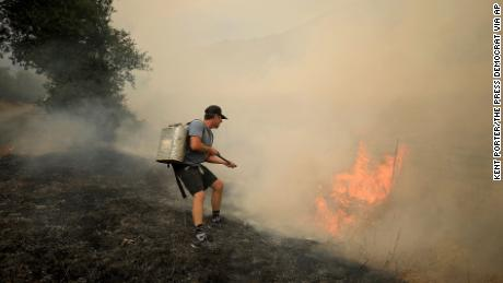 Tony Leonardini, a resident of Chiles Valley, works on a spot fire during the Hennessy fire as thunderstorm winds fan the fire, Monday, August 17, 2020 in Napa County, California. California firefighters are battling destructive wildfires as a lengthening heat wave roasts the state. (Kent Porter/The Press Democrat via AP)