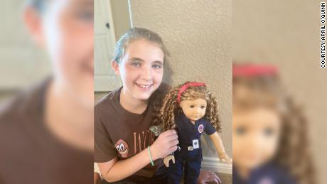 American Girl doll based on EMS provider April O'Quinn held by her niece Lacey.