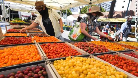 People wearing face coverings shop for tomatoes at the Santa Monica Farmers' Market in Santa Monica, California, August 1, 2020 during the coronavirus pandemic.