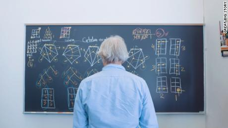 Dave Bayer stands in front of a blackboard covered in Hagoromo chalk.