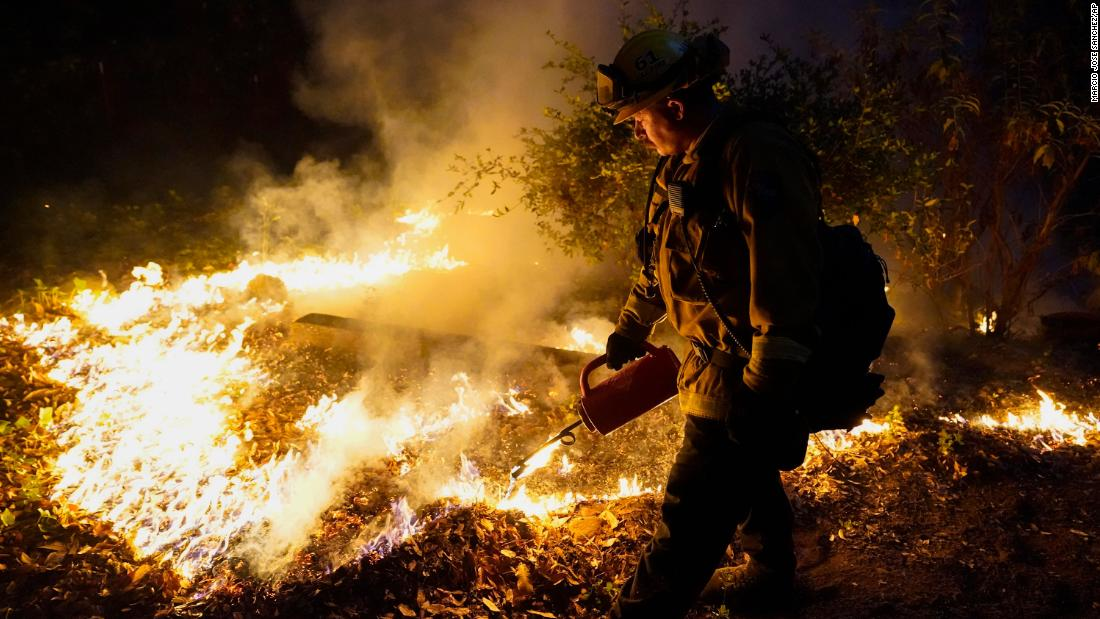 A firefighter monitors the advance of a fire in Boulder Creek on August 21.