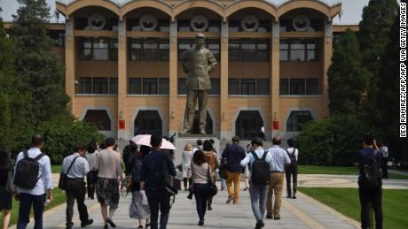 Students walk towards a statue of the late Chairman Mao Zedong at the Central Party School in Beijing.