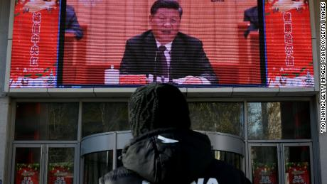A man stands and watches a large screen during President Xi Jinping's speech commemorating the 40th anniversary of China's policy of reform and opening on December 18, 2018.