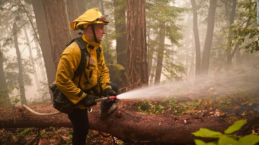 Karol Markowski of the South Pasadena Fire Department hoses down hot spots while battling the CZU Lightning Complex fires in Boulder Creek, Kalifornië, on August 22.