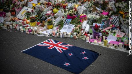 A New Zealand flag is placed next to flowers and tributes near Al Noor Mosque on March 18, 2019 in Christchurch, New Zealand.