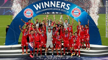 Manuel Neuer lifts the Champions League trophy in front of his team.