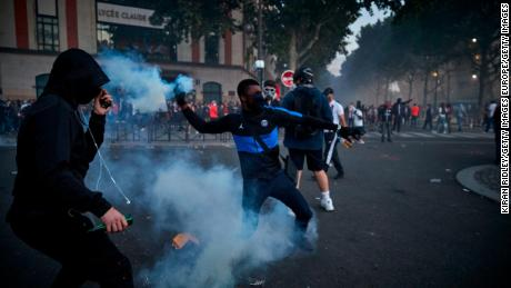 PARIS, FRANCE - AUGUST 23: A Paris Saint Germain fan throws a tear gas shell towards French Riot Police during violent confrontations between police and fans outside PSG's Parc de Princes Stadium as the Champions League Final was being played on August 23, 2020 in Paris, France. Paris Saint German football team have reached the 2019/20 UEFA Champions League finals for the first time in their history, just eleven days after celebrating their 50th Anniversary, taking on five-time winners Bayern Munich at the Estádio da Luz in Lisbon. (Photo by Kiran Ridley/Getty Images)