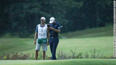 As the rain falls on them, Johnson lines up a putt with the help of  caddie Austin Johnson on the 18th green.