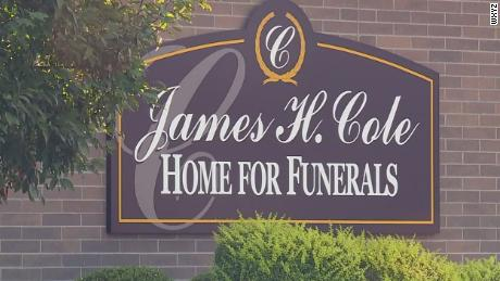 Firefighters on leave after a woman thought to be dead was found breathing at a funeral home