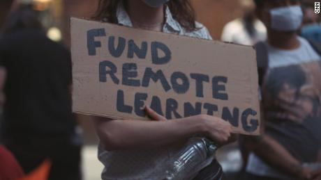 """A teacher holds a sign reading """"fund remote learning"""" at a protest on August 20, 2020."""