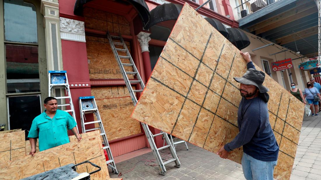 Cesar Reyes, destra, carries a sheet of plywood as he helps install window coverings at a business in Galveston.