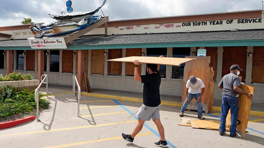 Nick Gaido, 剩下, helps board up windows at his seafood restaurant in Galveston.
