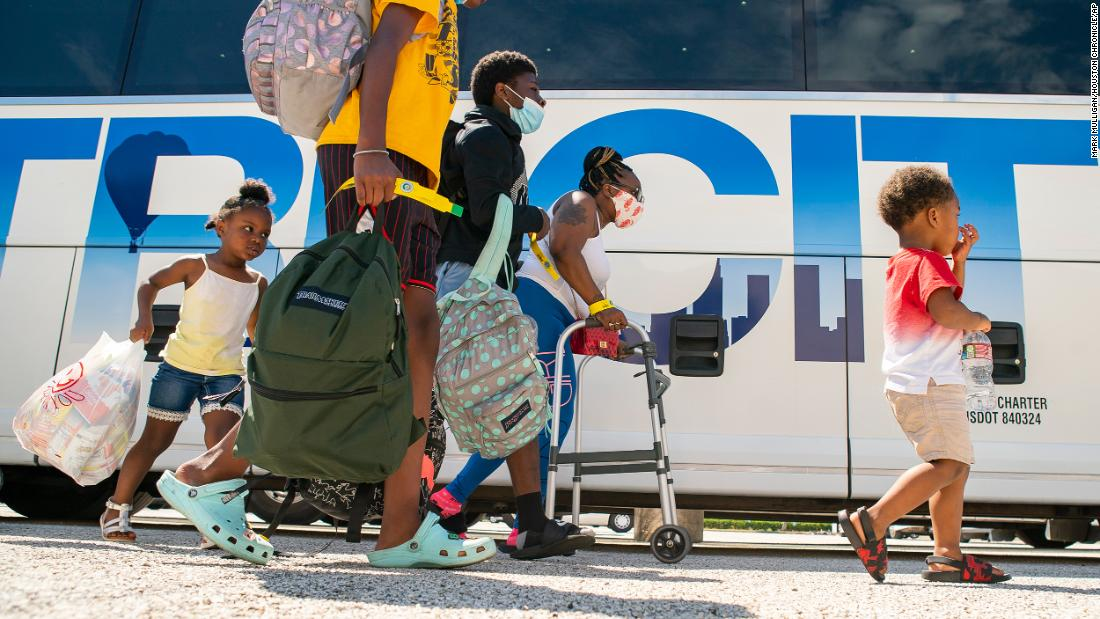 A family walks to a charter bus that would take them from Galveston Island to Austin.