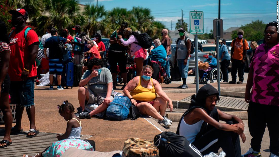 People wait to board a bus to leave Galveston.