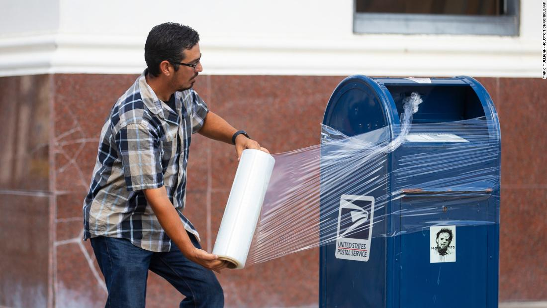 A US Postal Service employee covers a mailbox with plastic wrap in Galveston, Texas. The plastic wrap signals that the final mail has been cleared from the box, and it prevents people from placing mail inside that could be lost in a flood.
