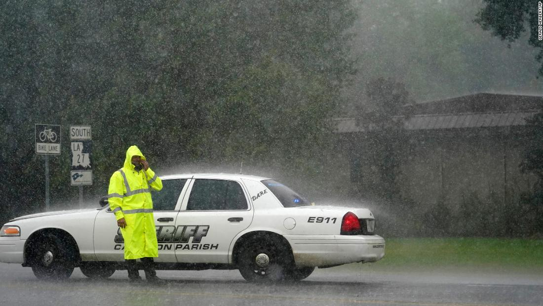 A sheriff's deputy wipes his face while manning a roadblock in Lake Charles on August 26.