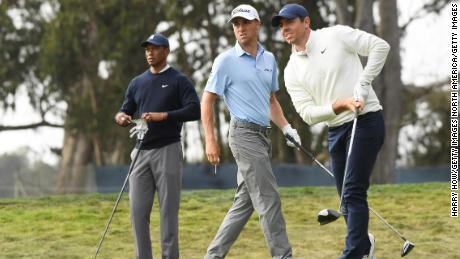 McIlroy reacts to his shot from the 12th tee at the 2020 PGA Championship in San Francisco as Thomas and Woods watch on.