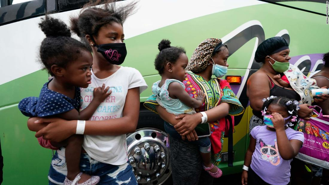 Families line up to board buses to evacuate Lake Charles on August 26.
