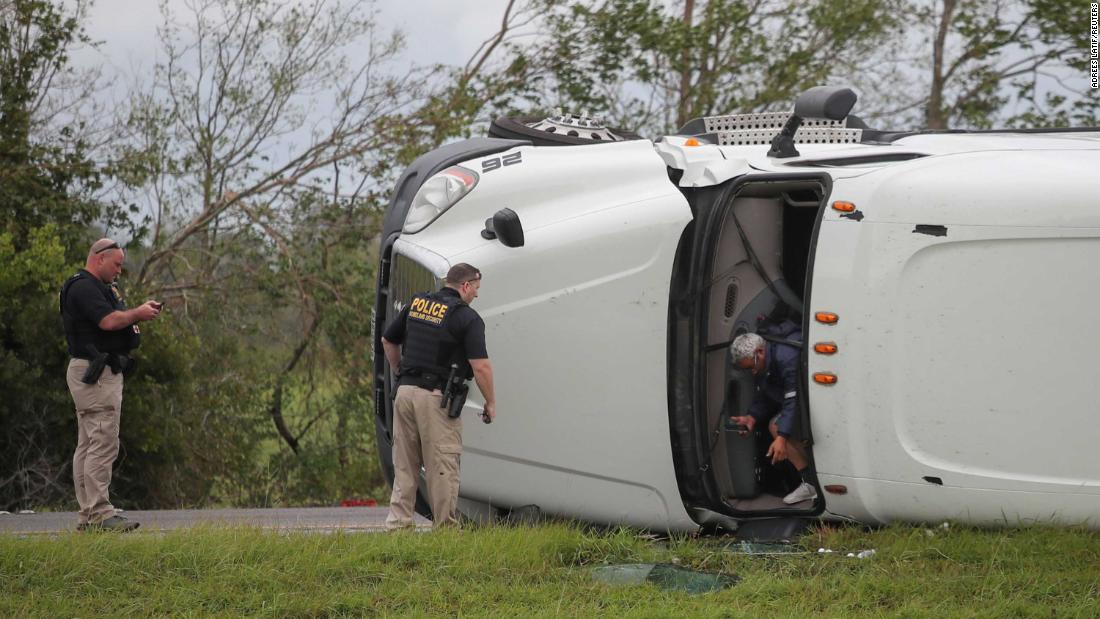 The driver of an overturned 18-wheeler exits his vehicle after police arrive to the scene along Interstate 10 in Vinton, Texas. Both the driver and a passenger suffered minor injuries.