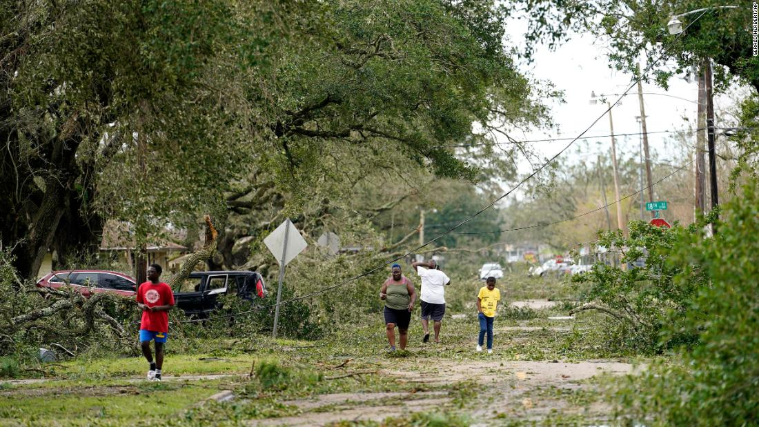 People survey the damage to their Lake Charles neighborhood on August 27.