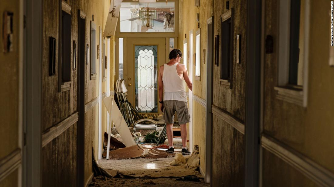 A man walks through a debris-filled hallway on the second floor of a Lake Charles church that lost its roof on August 27.
