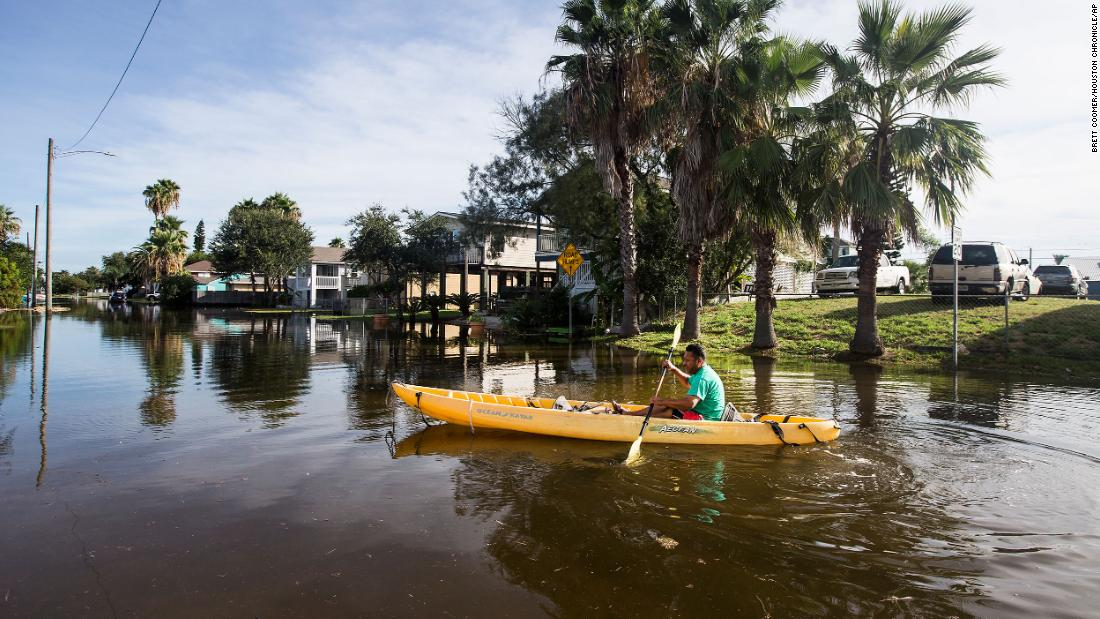 Martin Almanza paddles a canoe through a flooded section of Galveston, 德州, on August 27.